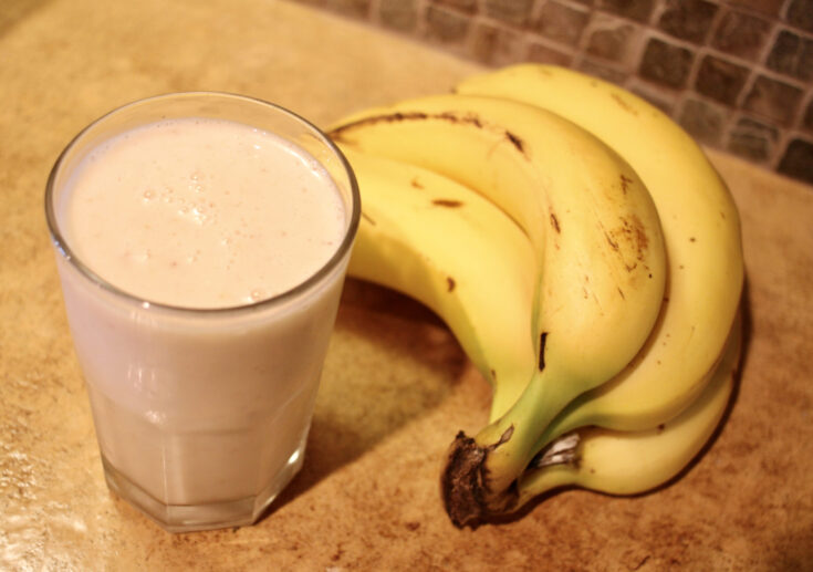 smoothie in glass with bananas on the side