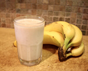 glass filled with smoothie and bananas