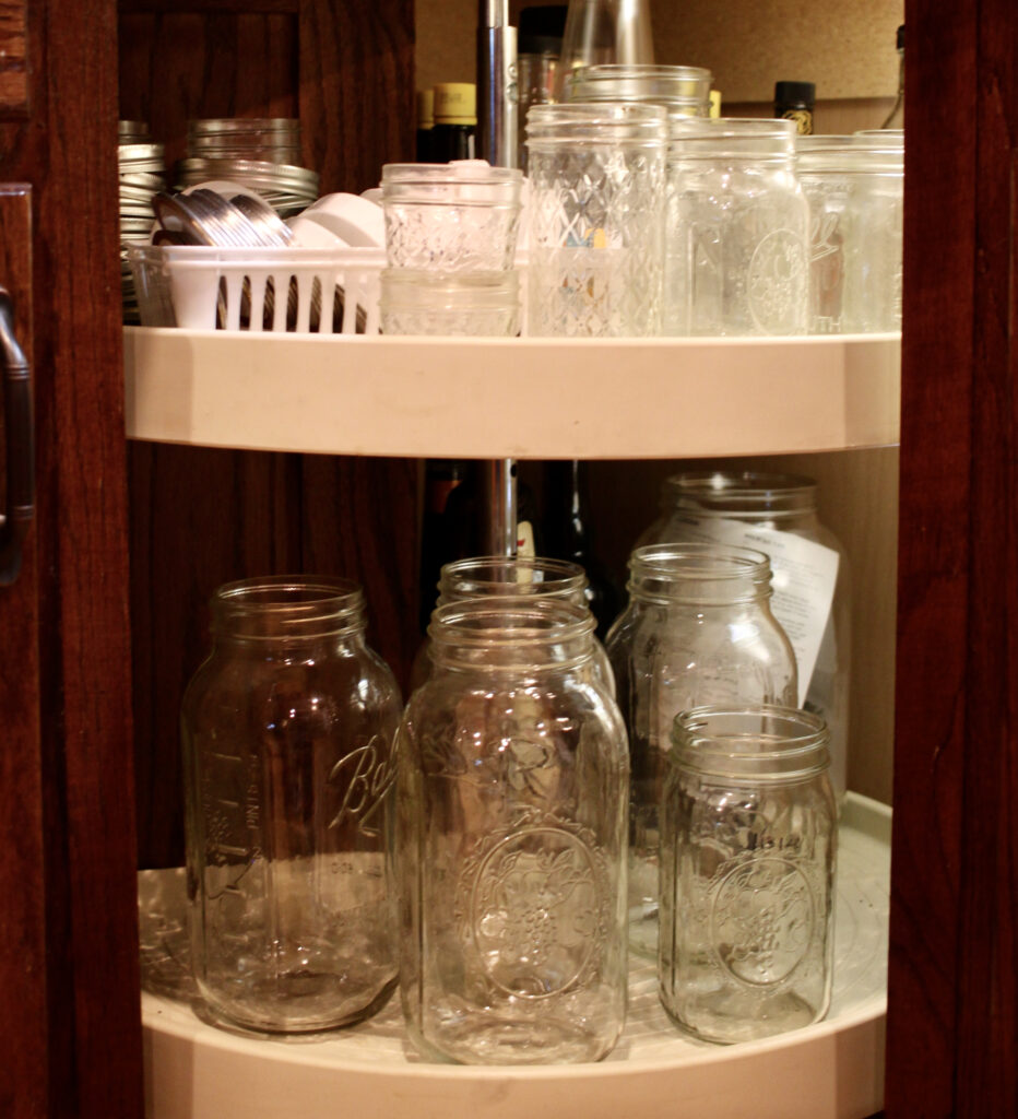 canning jars and lids inside a cabinet