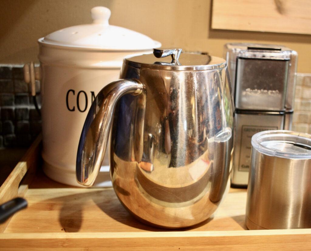 French press, yeti coffee mug and grinder on a wood tray